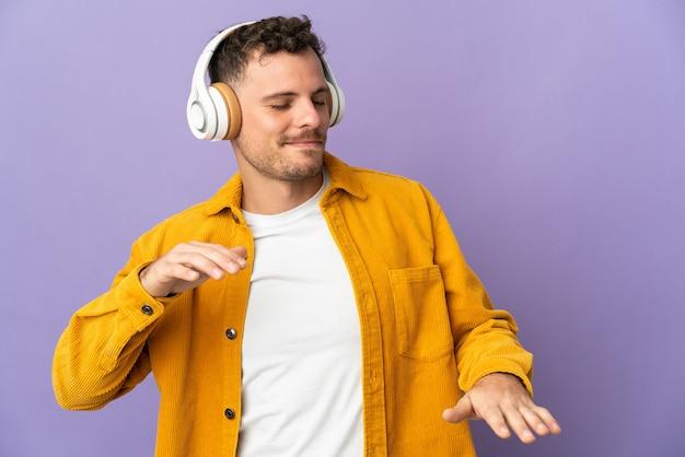 Joven guapo caucásico en púrpura escuchando música y bailando