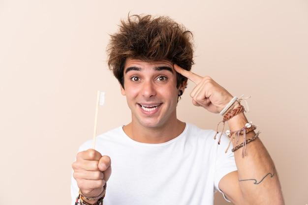 Joven guapo cepillarse los dientes con la intención de darse cuenta de la solución