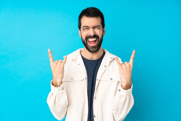 Joven guapo con chaqueta de pana blanca sobre pared azul aislada haciendo gesto de rock
