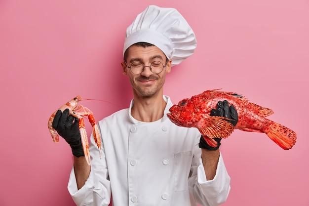 Joven guapo chef sosteniendo cangrejos crudos aislado