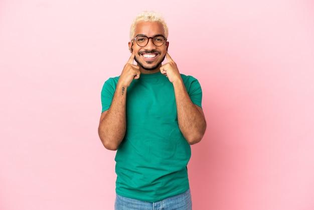 Joven guapo colombiano aislado sobre fondo rosa sonriendo con una expresión feliz y agradable