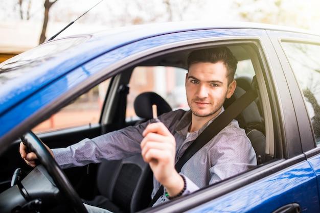Joven guapo conduciendo su auto nuevo, sosteniendo las llaves