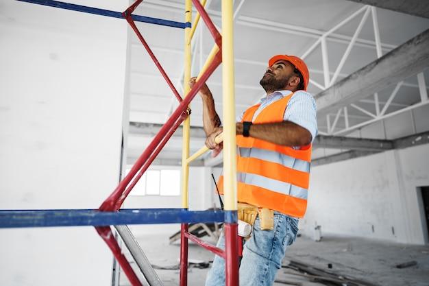 Joven guapo constructor escalada en andamios en el sitio de construcción