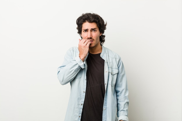 Joven guapo contra un fondo blanco mordiendo las uñas, nervioso y muy ansioso.