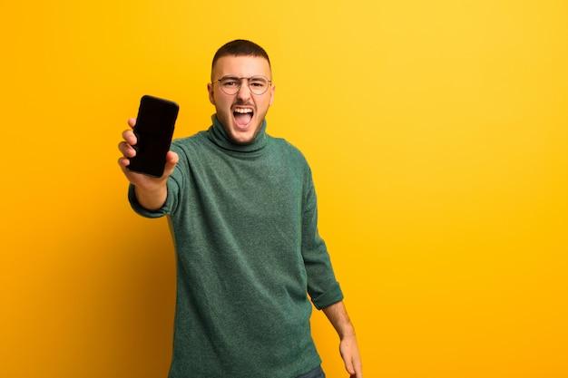 Joven guapo contra la pared plana con un teléfono inteligente