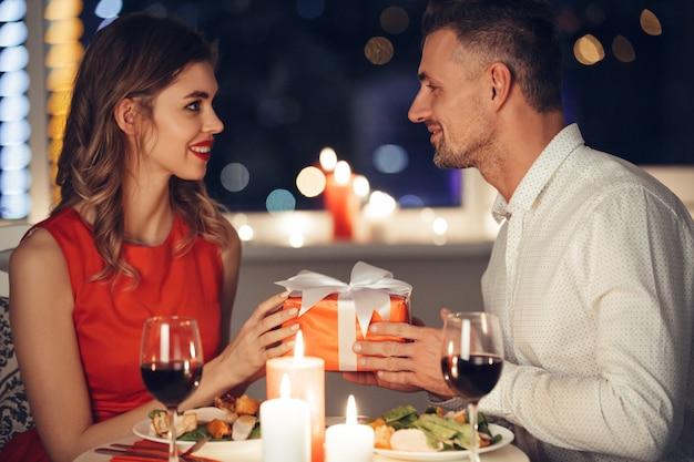 Joven guapo dando regalo a su amiga mientras cena romántica