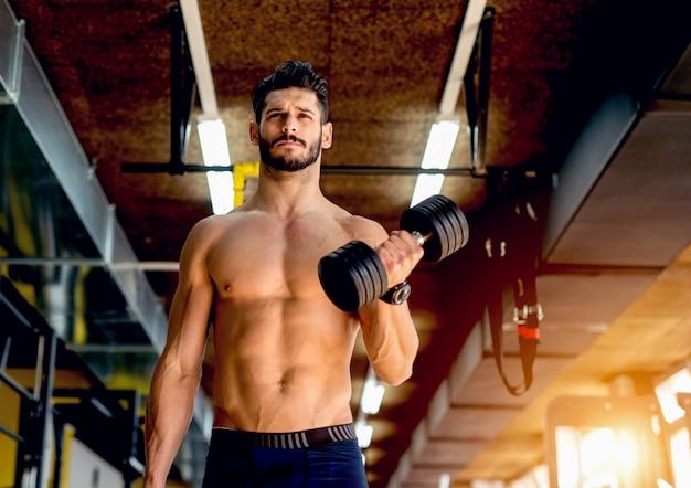 Joven guapo deportista levantando peso trabajando duro en el gimnasio
