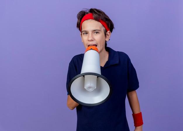 Joven guapo deportivo con diadema y muñequeras con aparatos dentales mirando al frente hablando por altavoz aislado en la pared púrpura