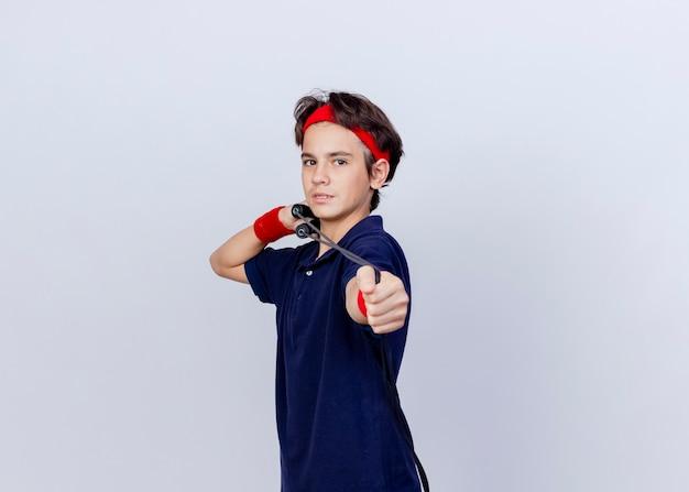 Joven guapo deportivo vistiendo diadema y muñequeras con aparatos dentales de pie en la vista de perfil tirando de la cuerda para saltar aislado sobre fondo blanco con espacio de copia