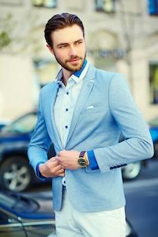 Joven guapo elegante en traje en la calle