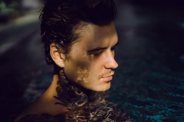 Joven guapo en tatuajes descansando en la piscina al aire libre.