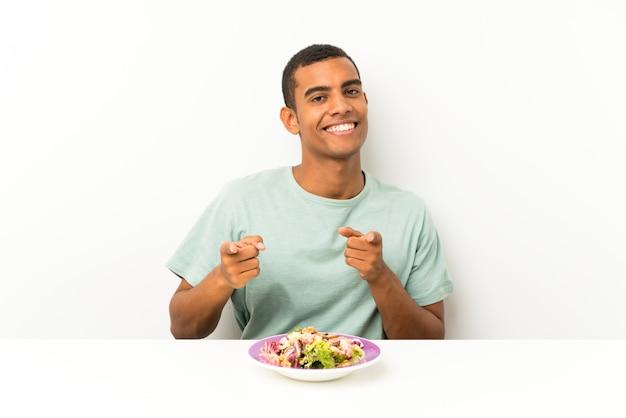 Joven guapo con ensalada en una mesa te señala con el dedo