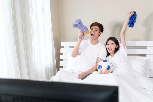 El joven y guapo esposo asiático y su bella esposa se sienten muy contentos por su equipo