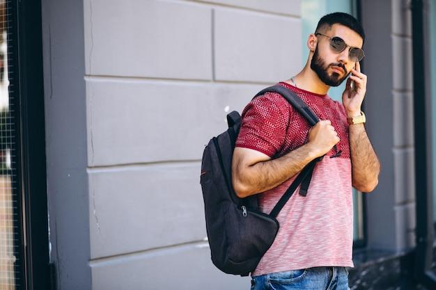Joven guapo estudiante barbudo con teléfono