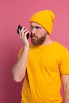 Joven guapo europeo sonriendo feliz escuchando mensajes de audio con smartphone en rosa