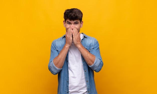 Joven guapo feliz y emocionado, sorprendido y asombrado cubriendo la boca con las manos, riendo con una expresión linda