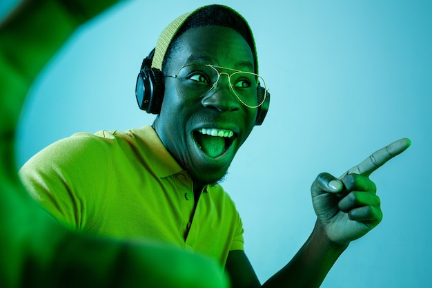 El joven guapo feliz sorprendido hipster hombre escuchando música con auriculares en el estudio con luces de neón.