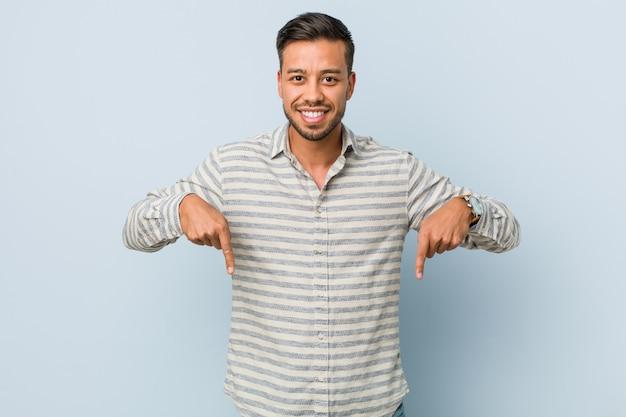 Joven guapo filipino apunta hacia abajo con los dedos, sentimiento positivo