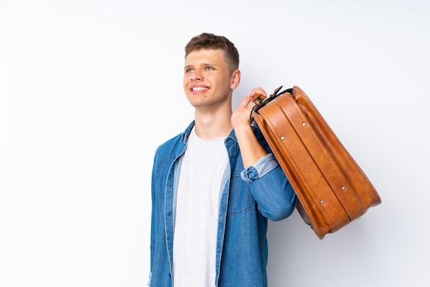 Joven guapo fondo blanco hombre sosteniendo un maletín vintage