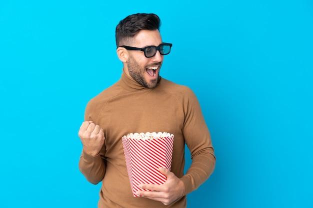 Joven guapo con gafas 3d y sosteniendo un gran cubo de palomitas de maíz mientras mira hacia el lado