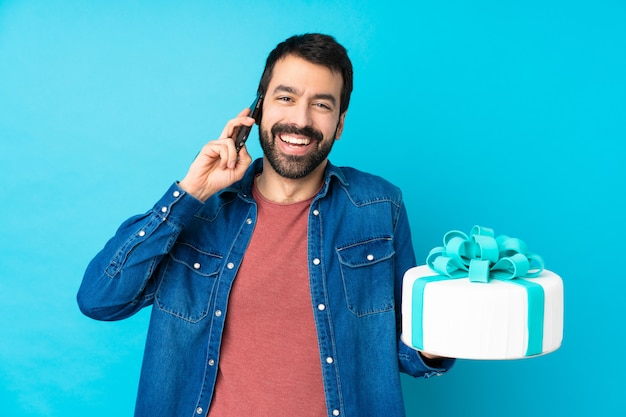 Joven guapo con un gran pastel sobre la pared azul aislada manteniendo una conversación con el teléfono móvil con alguien