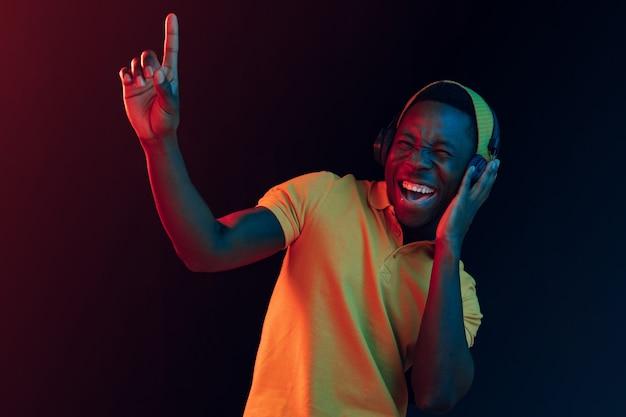 El joven guapo hipster feliz escuchando música con auriculares en el estudio negro con luces de neón. discoteca, club nocturno, estilo hip hop, emociones positivas, expresión facial, concepto de baile
