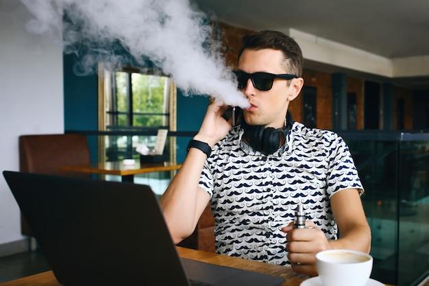 Joven guapo hipster hombre insunglasse sentado en la cafetería con una taza de café, vaping y libera una nube de vapor