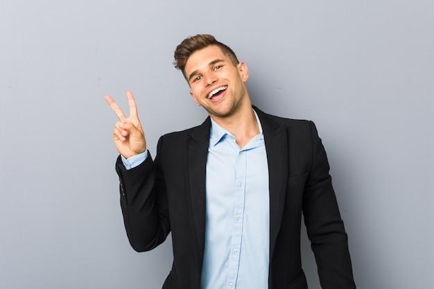 Joven guapo hombre caucásico alegre y despreocupado mostrando un símbolo de paz con los dedos.
