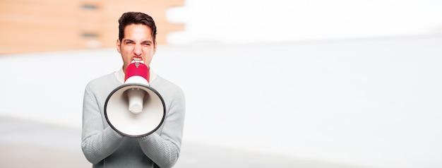 Joven guapo hombre curtido con un megáfono
