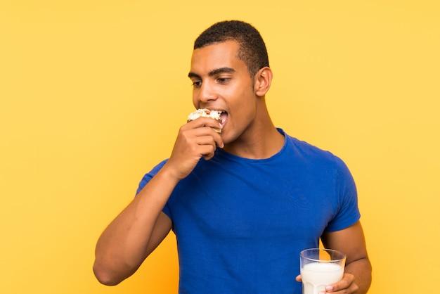 Joven guapo hombre morena sobre pared amarilla desayunando leche y sosteniendo pastel de muffin