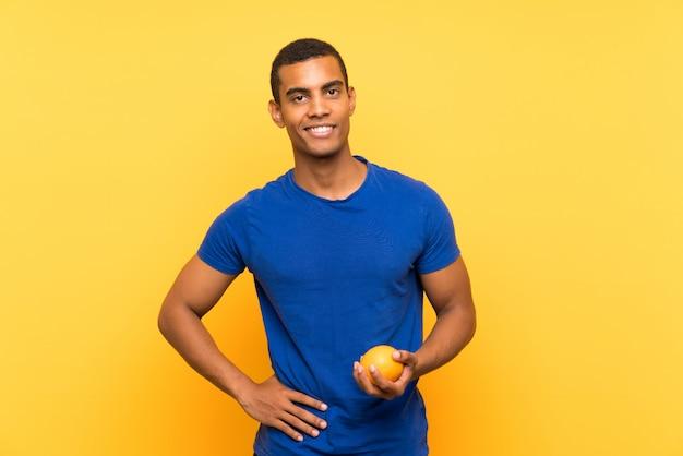 Joven guapo hombre morena sobre pared amarilla sosteniendo una naranja