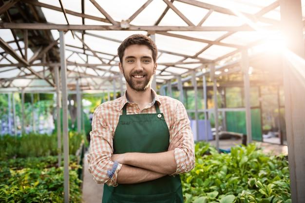Joven guapo jardinero sonriendo, posando con los brazos cruzados entre flores