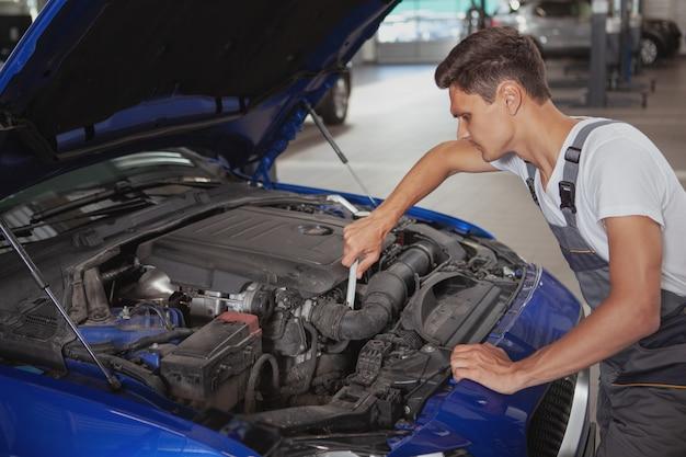 Joven guapo mecánico reparando el vehículo en su garaje