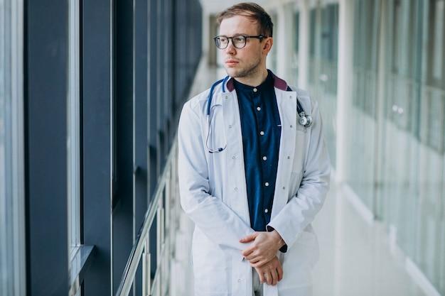 Joven guapo médico con estetoscopio en clínica