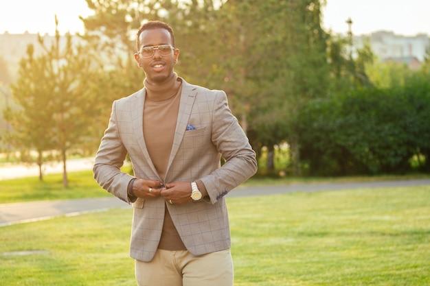 Un joven y guapo modelo con estilo afroamericano con un elegante traje en un parque de verano. hombre de negocios hispano latinoamericano hombre negro caminando después del trabajo en la oficina.