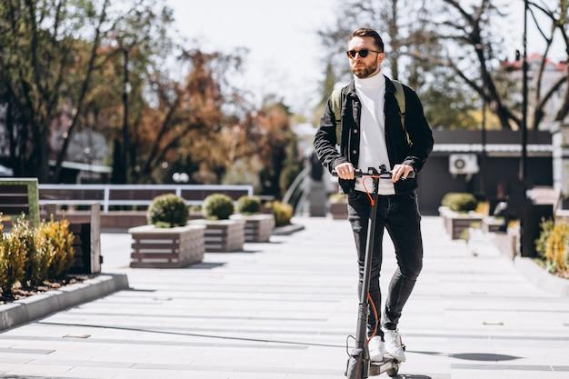 Joven guapo montando en moto en el parque