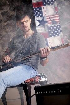 Joven guapo músico tocando la guitarra eléctrica sobre un fondo oscuro