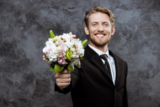 Joven guapo novio sonriendo, con ramo de novia