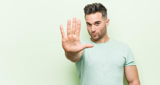 Joven guapo ongreen de pie con la mano extendida que muestra la señal de stop, impidiéndole.