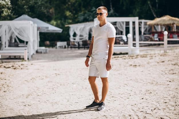 Joven guapo parado en la playa por el parque