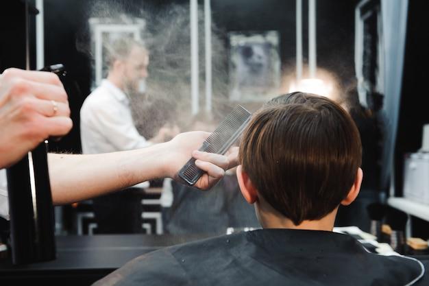 Joven guapo peluquero haciendo corte de pelo de niño en peluquería