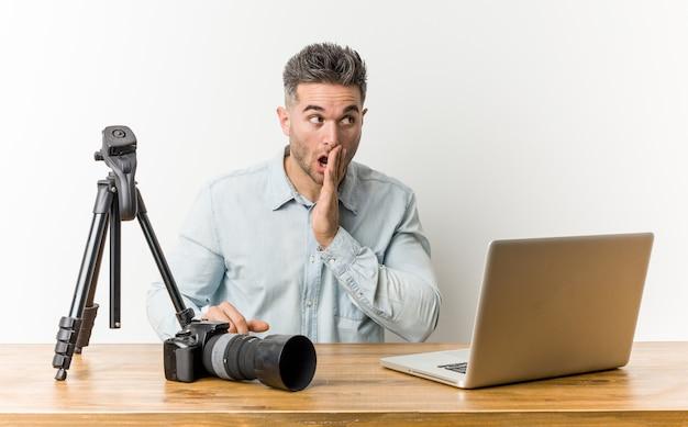 Joven y guapo profesor de fotografía está diciendo una noticia secreta de frenado caliente y está mirando a un lado