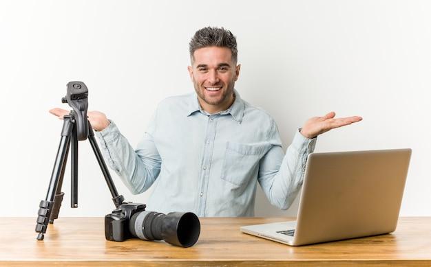 Joven y guapo profesor de fotografía hace escala con los brazos, se siente feliz y confiado.