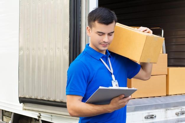 Joven guapo repartidor llevando caja de paquetería