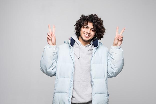 Joven guapo rizado alegre y despreocupado mostrando un símbolo de paz con los dedos aislados en la pared blanca
