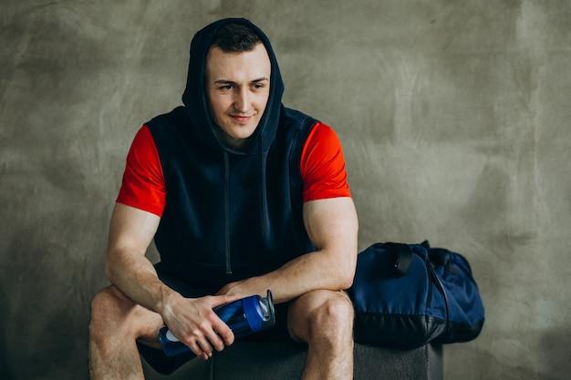 Joven guapo en ropa deportiva en el gimnasio