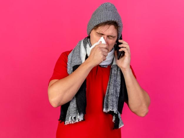 Joven guapo rubio enfermo con gorro de invierno y bufanda hablando por teléfono limpiando la nariz con una servilleta con los ojos cerrados aislados en la pared rosa con espacio de copia