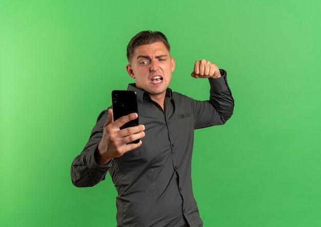 Joven guapo rubio molesto mira el teléfono y mantiene el puño listo para perforar aislado sobre fondo verde con espacio de copia