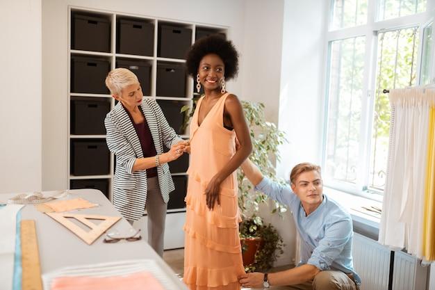 Joven guapo sastre y su colega ajustando un vestido confeccionado a un tamaño perfecto