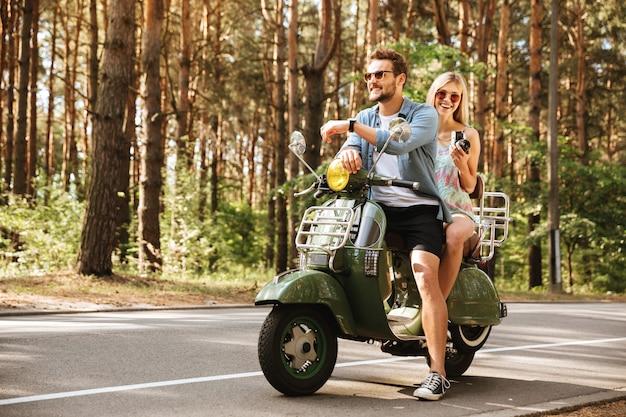 Joven guapo en scooter con novia con cámara